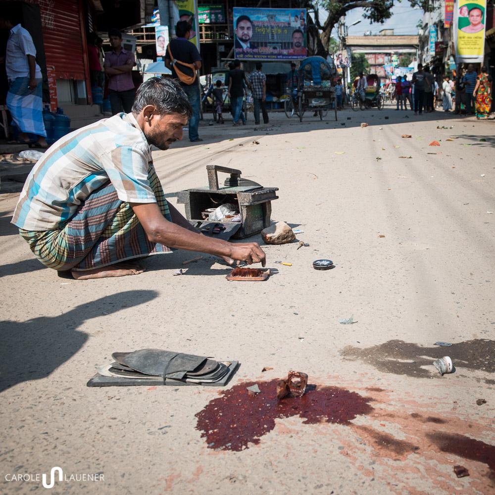 Ein Schuhmacher sucht nach einem Strassenscharmützel den Inhalt seines Werkzeugkastens zusammen.