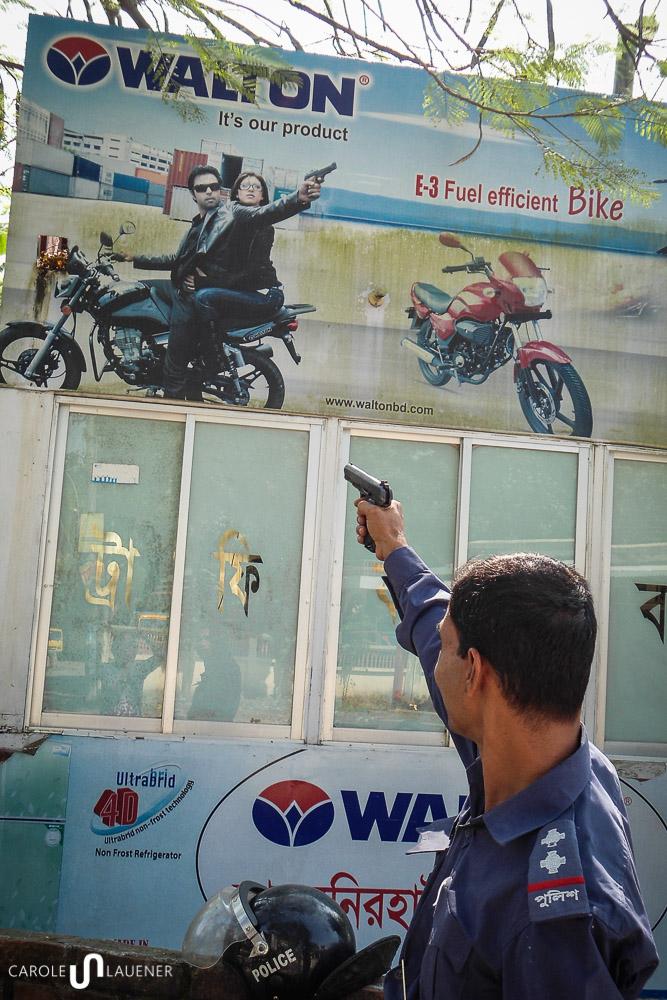 Obwohl Moshiur hofft, seine Waffe nie gebrauchen zu müssen, posiert er für ein Foto vor seiner Policebox mit gezückter Waffe.