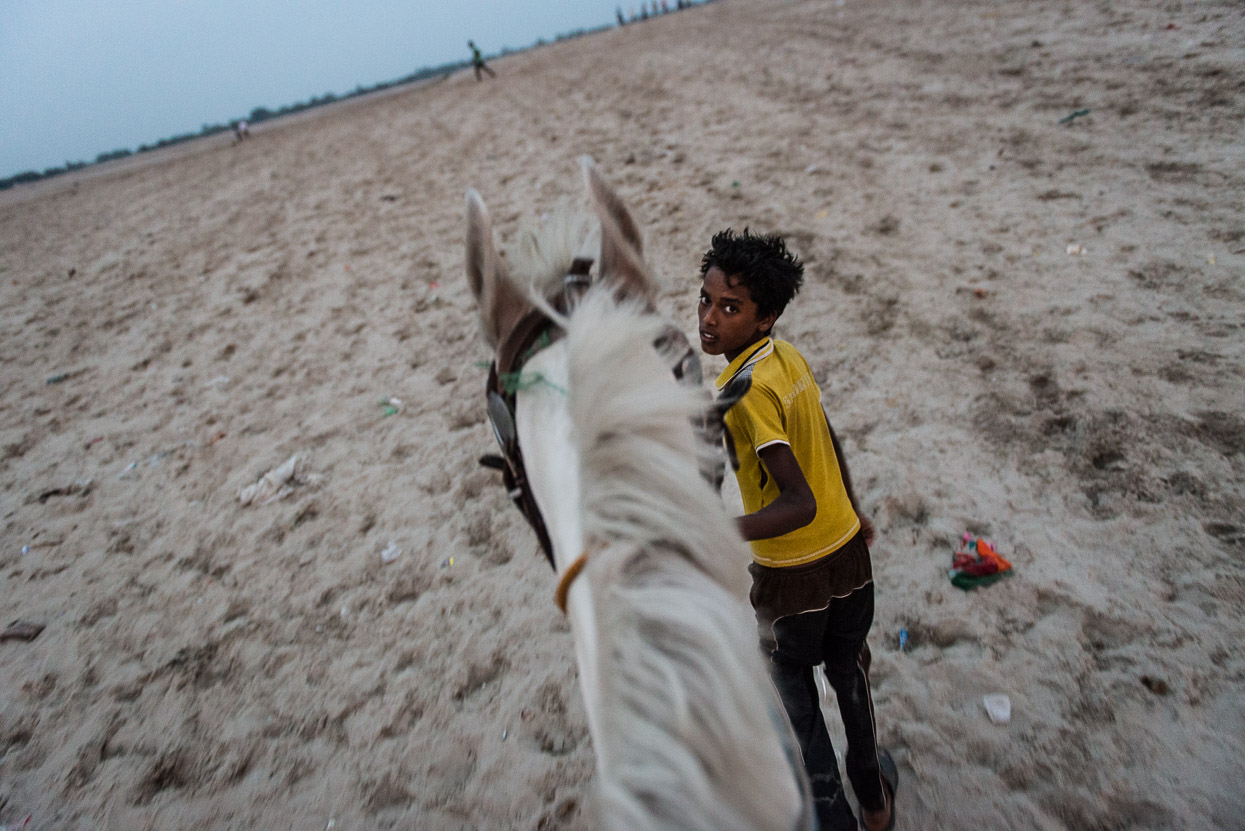 Horse riding on the river bank of Ganges opposite of Varanasi